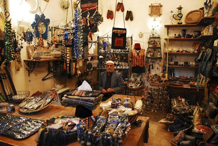 In this picture taken on March 4, 2007, a Syrian vendor sits inside his shop, at the souk in the old city of Aleppo city, Syria. Fires sparked by clashes between government troops and rebels raged through the medieval marketplace of Aleppo on Saturday, Sept. 29, 2012, destroying hundreds of shops lining the vaulted passageways where foods, fabrics, perfumes and spices have been sold for centuries, activists said. (AP Photo/Muzaffar Salman)