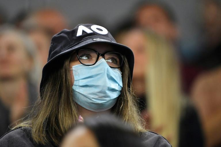 A fan wearing a face mask watches Italy's Matteo Berrettini play South Africa's Kevin Anderson at the Australian Open