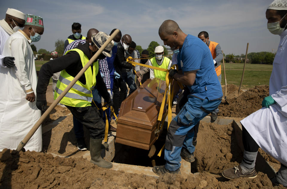 """FILE - In this Friday, April 24, 2020 file photo, mourners set down the coffin of a Guinean man, who died of COVID-19 and who the family did not wish to identify by name, during a funeral at the cemetery of Evere, Belgium. After the European Union passed the death toll of half a million citizens lost to the coronavirus on Wednesday, Feb. 10, 2021, the EU Commission chief said that stalling rollout of the vaccines could be partly blamed on the bloc being over-optimistic, over-confident and plainly """"too late."""" (AP Photo/Virginia Mayo)"""