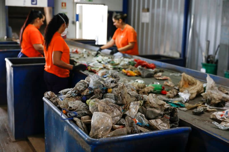 FILE PHOTO: Workers separate different types of plastic at Extruplas plant in Seixal