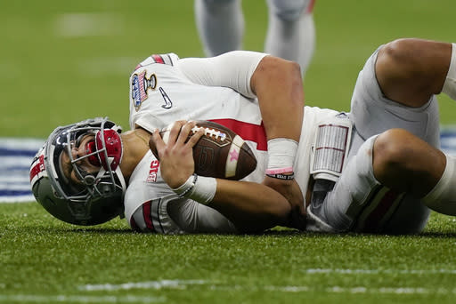 Ohio State quarterback Justin Fields grimaces after getting hit by Clemson linebacker James Skalski during the first half of the Sugar Bowl NCAA college football game Friday, Jan. 1, 2021, in New Orleans. Skalski was ejected from the game for targeting. (AP Photo/Gerald Herbert)