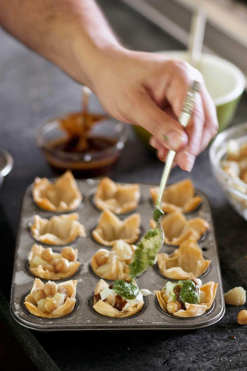 """<p>Flaky phyllo cups corral zesty chickpeas, potatoes, yogurt, and chutney in this take on the Indian street snack papri chaat.</p><p><a href=""""https://www.womansday.com/food-recipes/food-drinks/recipes/a38910/spicy-chickpea-potato-phyllo-cups-recipe-clv0712/"""" rel=""""nofollow noopener"""" target=""""_blank"""" data-ylk=""""slk:Get the Spicy Chickpea-and-Potato Phyllo Cups recipe."""" class=""""link rapid-noclick-resp""""><em>Get the Spicy Chickpea-and-Potato Phyllo Cups recipe.</em></a> </p>"""
