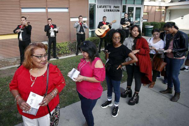 PHOTO: Latino voters Griselda Sanchez, left and Evelyn Franco, second from left, wait in line while being serenaded by mariachis at the Lafayette Park Gymnasium polling station in Los Angeles, Calif., Nov. 6, 2018. (Mike Nelson/EPA via Shutterstock)