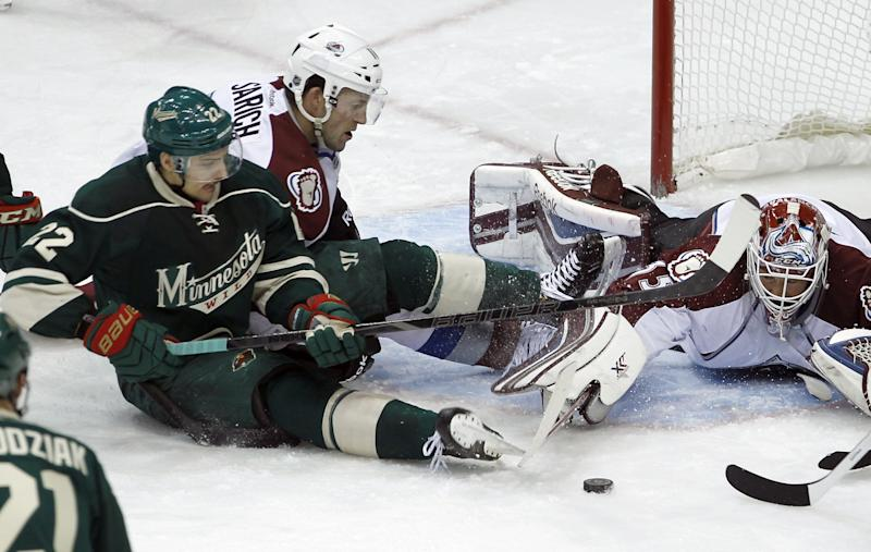 Colorado Avalanche goalie Jean-Sebastien Giguere, right, uses his stick to get the puck away from Minnesota Wild right wing Nino Niederreiter (22), of Switzerland, as Avalanche defenseman Cory Sarich watches during the second period of an NHL hockey game in St. Paul, Minn., Friday, Nov. 29, 2013. (AP Photo/Ann Heisenfelt)