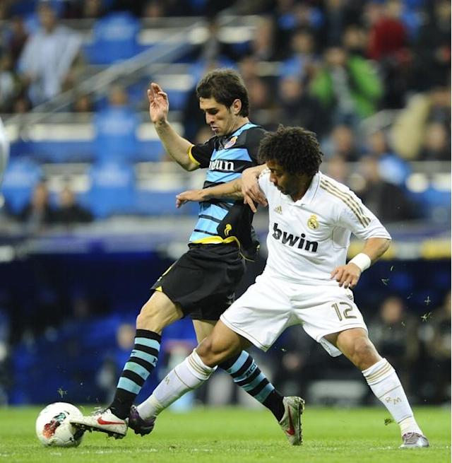 Real Madrid's Brazilian defender Marcelo (R) fights for the ball with Espanyol's Argentinian defender Juan Forlin on March 4, 2012 during a Spanish league football match at the Santiago Bernabeu stadium in Madrid. (Photo by Pierre-philippe Marcou /AFP/Getty Images)