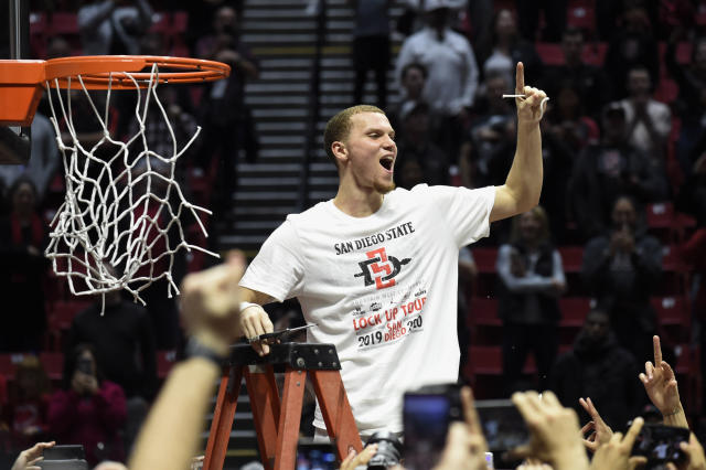 San Diego State guard Malachi Flynn (22) holds a piece of the net after the team defeated New Mexico 82-59 in an NCAA college basketball game to win the Mountain West Conference championship, Tuesday, Feb. 11, 2020, in San Diego. (AP Photo/Denis Poroy)