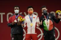 Gold medalist Lyu Xiaojun of China, center is flanked by silver medalist Zacarias Bonnat Michel of Dominican Republic, left, and bronze medalist Antonino Pizzolato of Italy, on the podium of the men's 81kg weightlifting event, at the 2020 Summer Olympics, Saturday, July 31, 2021, in Tokyo, Japan. (AP Photo/Luca Bruno)