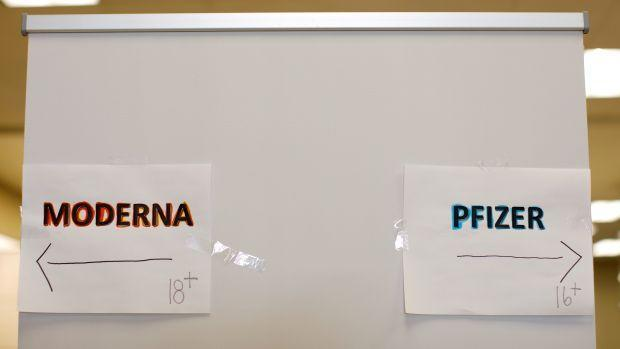 signs show directions for moderna and pfizer shots