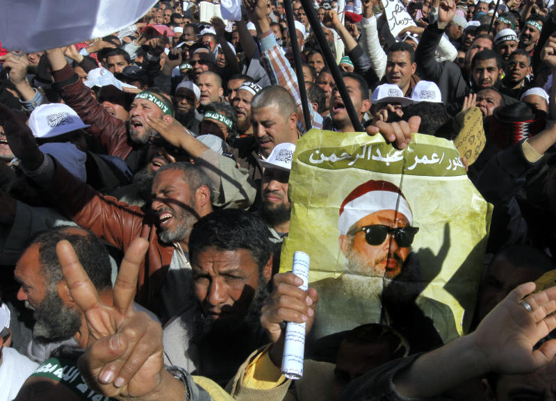 "Supporters of Sheik Omar Abdel-Rahman, a blind Egyptian cleric jailed in the United States for planning a campaign of bombings, call for his release while one demonstrator holding a poster with his image, during a rally outside Cairo University in Cairo, Egypt, Friday, Feb. 15, 2013. Around 5,000 mostly hardline Islamists are rallying in Egypt against a recent wave of protests that has killed around 70 people. Arabic reads, ""Omar Abdel-Rahman."" (AP Photo/Amr Nabil)"