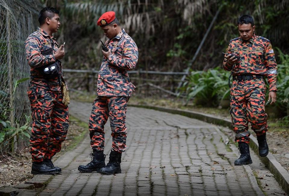 Members of a Malaysian rescue team listen to their radios at the Timpohon gate checkpoint after an earthquake in Kundasang, a town in the district of Ranau on June 6, 2015. (AFP Photo/Mohd Rasfan)