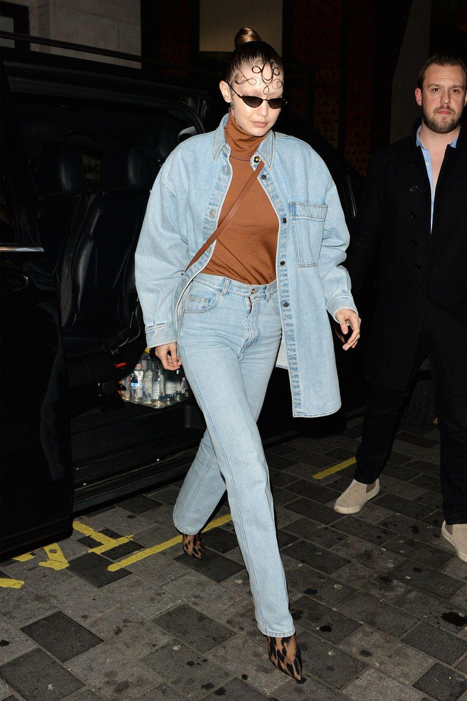 <p>In a light-wash denim jacket, brown turtleneck, matching jeans, and leopard print boots. </p>