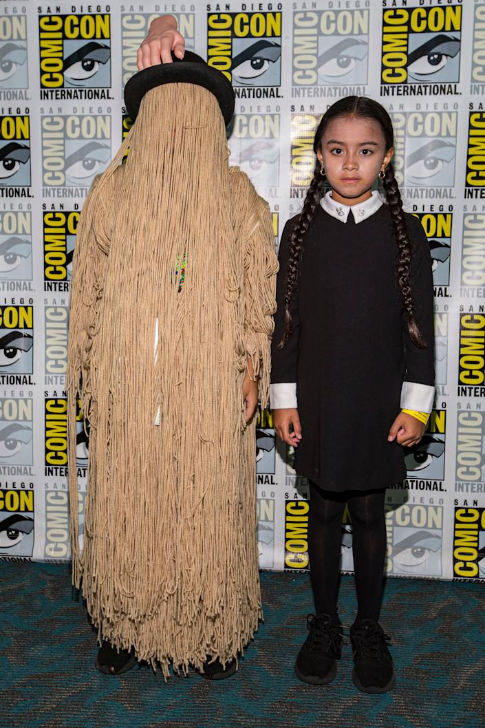 """Young cosplayers Ron Pizarro (L) and Mya Pizarro dressed as Cousin It and Wednesday Addams from """"The Addams Family."""""""