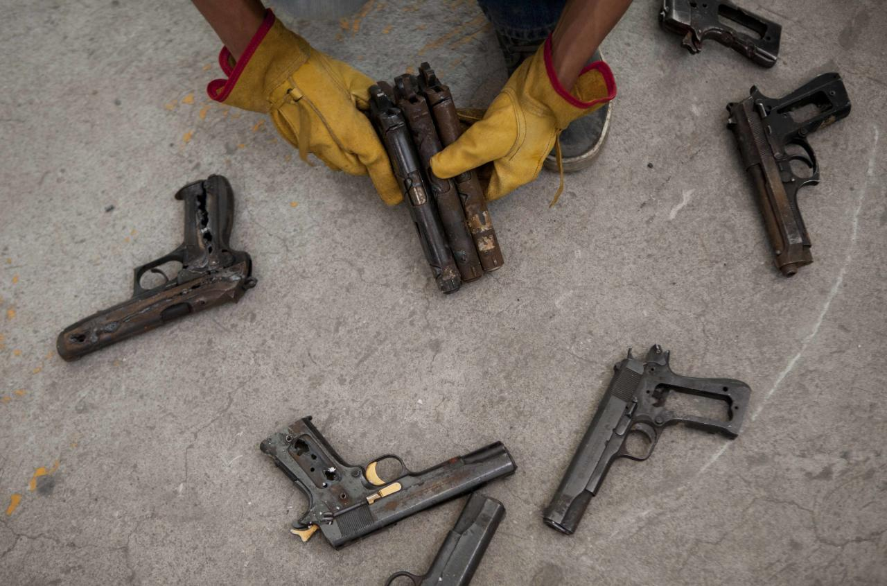 "A worker organizes a set of seized guns in the workshop of Mexican sculptor Pedro Reyes, in Mexico City, Tuesday, Feb. 13, 2013. The guns that have caused so many deaths in northern Mexico are transformed into musical instruments by Reyes. ""It's important to consider that many lives were taken with these weapons, as if a sort of exorcism was taking place,"" says Reyes in a description of his project titled, ""Disarm."" The Mexican artist said he was able to choose his instruments from about 6,700 guns that were turned in or seized by the army and police in Ciudad Juarez, a city of about 1.3 million people that averaged about 10 killings a day at the height of the violence. (AP Photo/Eduardo Verdugo)"
