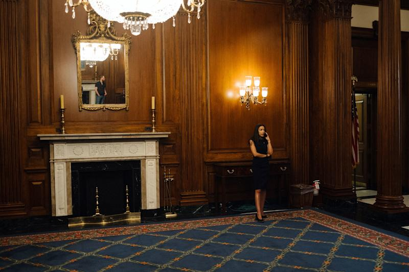 Ocasio-Cortez takes a phone call in the Rayburn Room in the Capitol, where her swearing in ceremony photos were taken in January 2019.