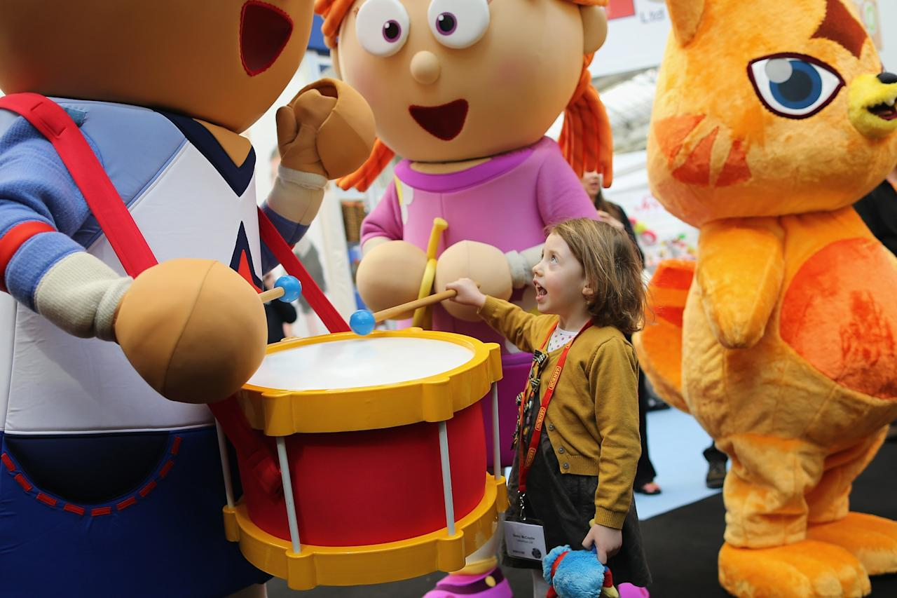 LONDON, ENGLAND - JANUARY 22:  Betsy McCredie, 4, from Glasgow interacts with life size cartoon characters during the 2013 London Toy Fair at Olympia Exhibition Centre on January 22, 2013 in London, England. The annual fair which is organised by the British Toy and Hobby Association, brings together toy manufacturers and retailers from around the world.  (Photo by Dan Kitwood/Getty Images)