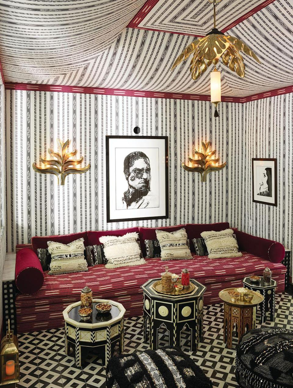 <p>Calling upon the embellished military tents treasured by African, Middle Eastern, and Roman leaders, Martyn Bullard Lawrence used an ikat print (Mariam Ikat) to give the room the illusion of more interesting architecture. Rounding out the boho feel, the California decorator paired vintage tea tables with lustrous embellishments. </p>