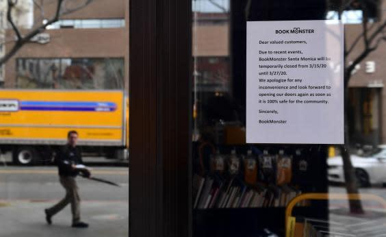 A sign for temporary closure is posted in front of the Book Monster bookstore in Santa Monica, California on 16 March 2020. (FREDERIC J BROWN/AFP via Getty Images)