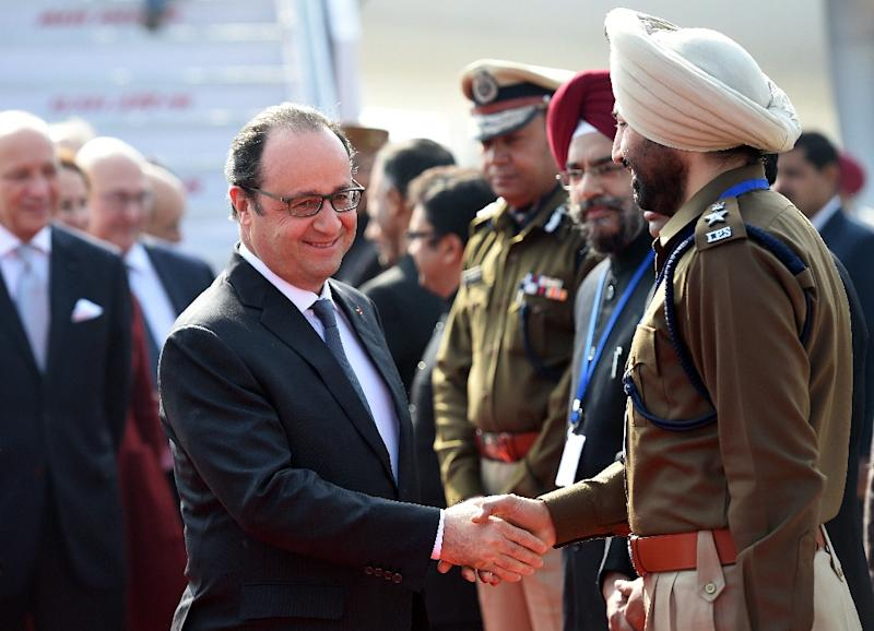 French President Francois Hollande (centre L) shakes hands with a member of the welcoming party on his arrival at the Indian military base in Chandigarh on January 24, 2016 (AFP Photo/Stephane De Sakutin)