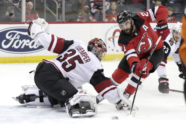Arizona Coyotes goaltender Darcy Kuemper (35) tries to make a save as New Jersey Devils right wing Kyle Palmieri (21) attacks during the second period of an NHL hockey game, Saturday, March 23, 2019, in Newark, N.J. (AP Photo/Julio Cortez)