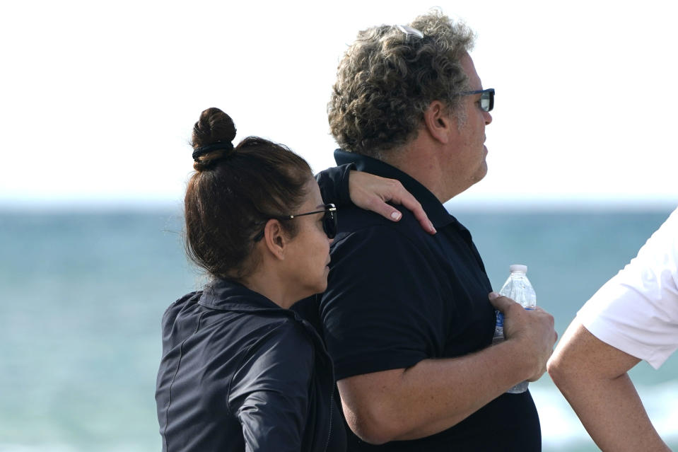 A couple, who asked not to be identified, stand on the beach near the Champlain Towers South Condo building, Saturday, June 26, 2021, in the Surfside area of Miami. The apartment building partially collapsed on Thursday. AP Photo/Lynne Sladky)