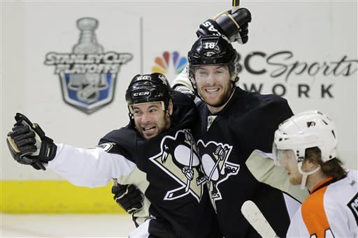 Pittsburgh Penguins' Steve Sullivan (26) celebrates his first-period goal with James Neal (18) as Philadelphia Flyers' Sean Couturier skates back to his bench during Game 5 of an opening-round NHL Stanley Cup hockey playoff series in Pittsburgh Friday, April 20, 2012. (AP Photo/Gene J. Puskar)