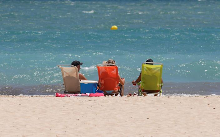 Sunbathers on a beach in Magaluf - Reuters