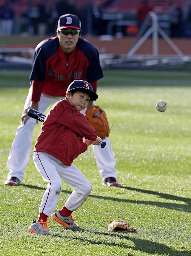 Boston Red Sox's Koji Uehara, of Japan, watches his son Kazuma hit before Game 2 of baseball's World Series Thursday, Oct. 24, 2013, in Boston. (AP Photo/David J. Phillip)