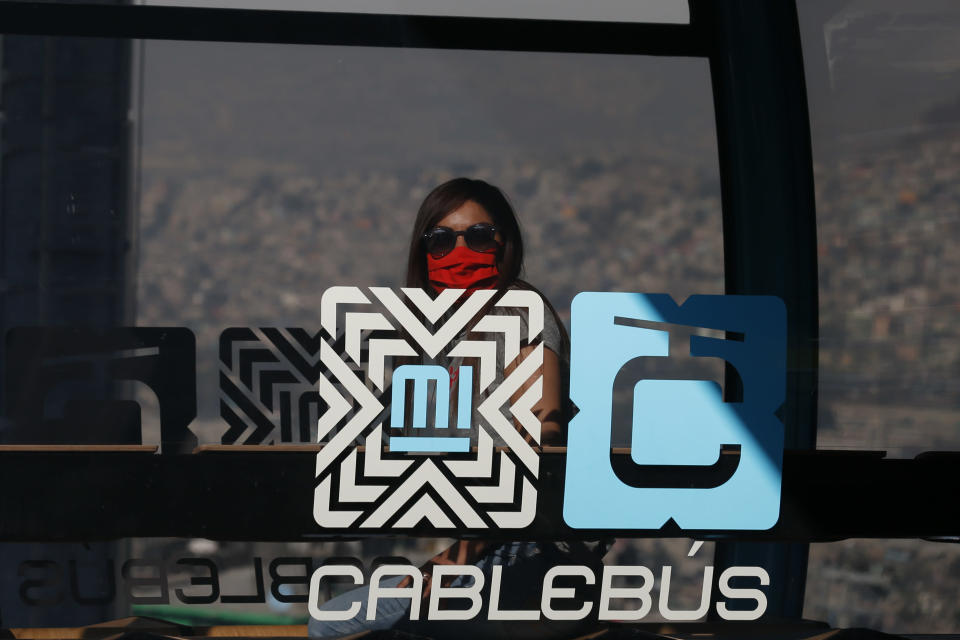 A journalist rides in a cable car between the Campos Revolucion and Tlalpexco stations, during the inauguration of a new aerial public transit system dubbed the Cablebus, in the Cuautepec neighborhood of northern Mexico City, Thursday, March 4, 2021. For the residents of Cuautepec, this new system, the first of four planned lines, will turn a commute to the nearest subway station, that can last up to two hours, into a 30-minute ride. (AP Photo/Rebecca Blackwell)