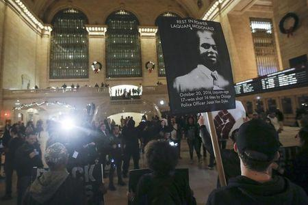 Black Lives Matter protesters chant slogans in Grand Central Terminal as they protest the 2014 death of Laquan McDonald from Chicago in the  Manhattan borough of New York December 14, 2015.     REUTERS/Carlo Allegri