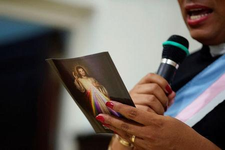 Alexya Salvador, a Brazilian trans pastor, holds a leaflet with an image of Jesus Christ during a mass in a church in Matanzas, Cuba, May 5, 2017. Picture taken on May 5, 2017. REUTERS/Alexandre Meneghini