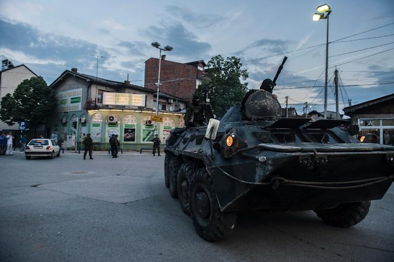 Macedonian troops in armored vehicles leave an area, still inaccessible, where fighting took place in Kumanovo on May 10, 2015 (AFP Photo/Armend Nimani)