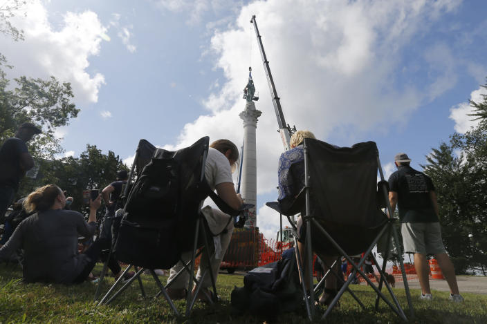 Spectators watch as crews work to remove the Confederate Soldiers & Sailors Monument in Libby Hill Park Wednesday July 8, 2020, in Richmond, Va. The 17-foot statue stands on a 73- foot pedestal overlooking downtown. The statue is one of several that will be removed by the city as part of the Black Lives Matter reaction. (AP Photo/Steve Helber)