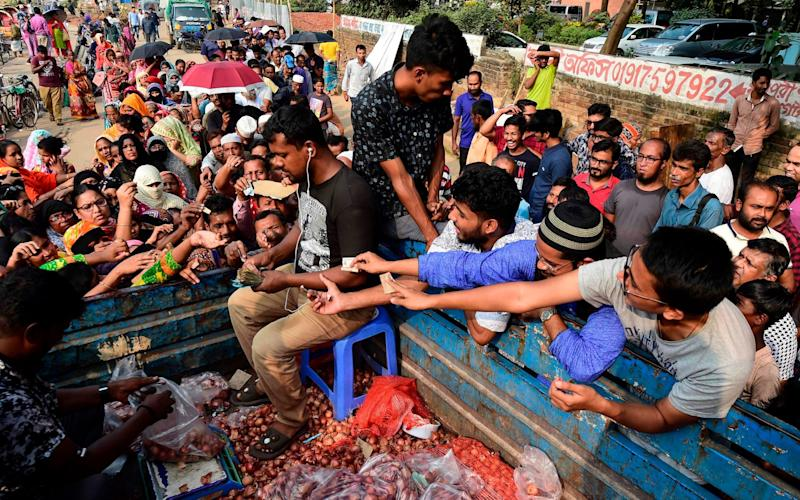 People scuffle as they purchase subsidised onions in Dhaka - AFP