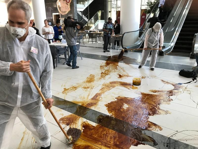 Protestors from climate change awareness collective Extinction Rebellion chant slogans and smear oil across the floor at the lobby of the Africa Oil Week conference in Cape Town