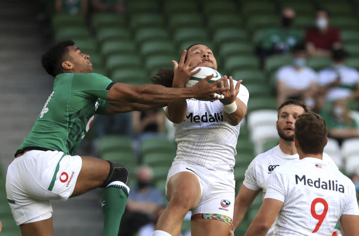 Ireland's Robert Baloucoune, left and USA's Mika Kruse compete for the ball, during the Rugby Union International Summer Series match between Ireland and USA, in Dublin, Ireland, Saturday July 10, 2021. (Donall Farmer/PA via AP)