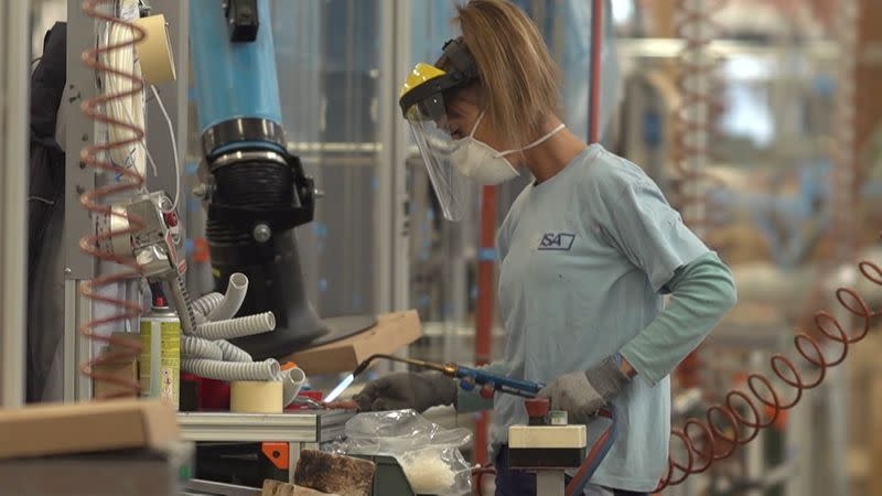 A worker, wearing a mask, uses a blowtorch inside the ISA factory in Bastia Umbra