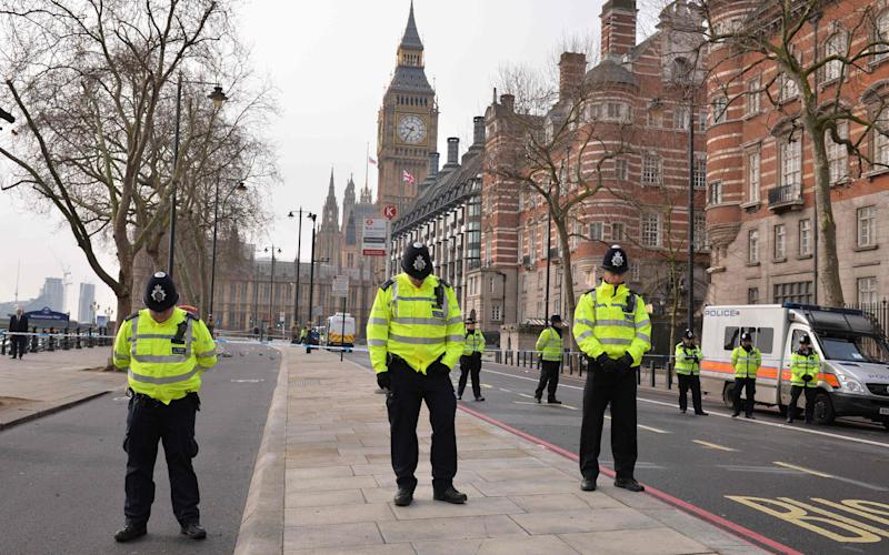 British police officers bow their heads as they stand near a police cordon directly ourside New Scotland Yard and within sight of the Houses of Parliament - AFP or licensors