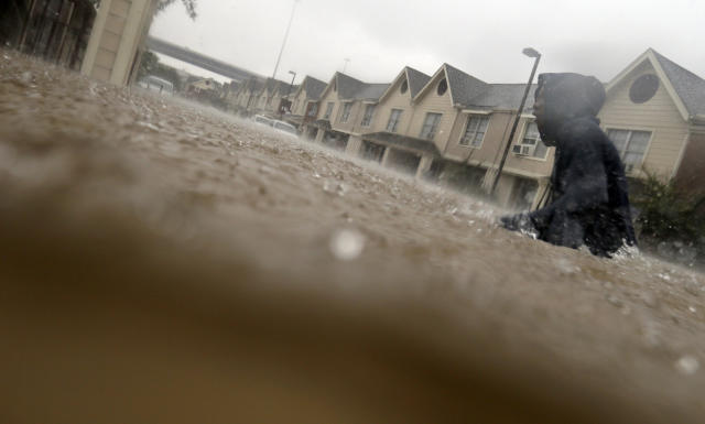 <p>A child makes his way through floodwaters from Tropical Storm Harvey while checking on neighbors at his apartment complex in Houston, Sunday, Aug. 27, 2017. (Photo: LM Otero/AP) </p>