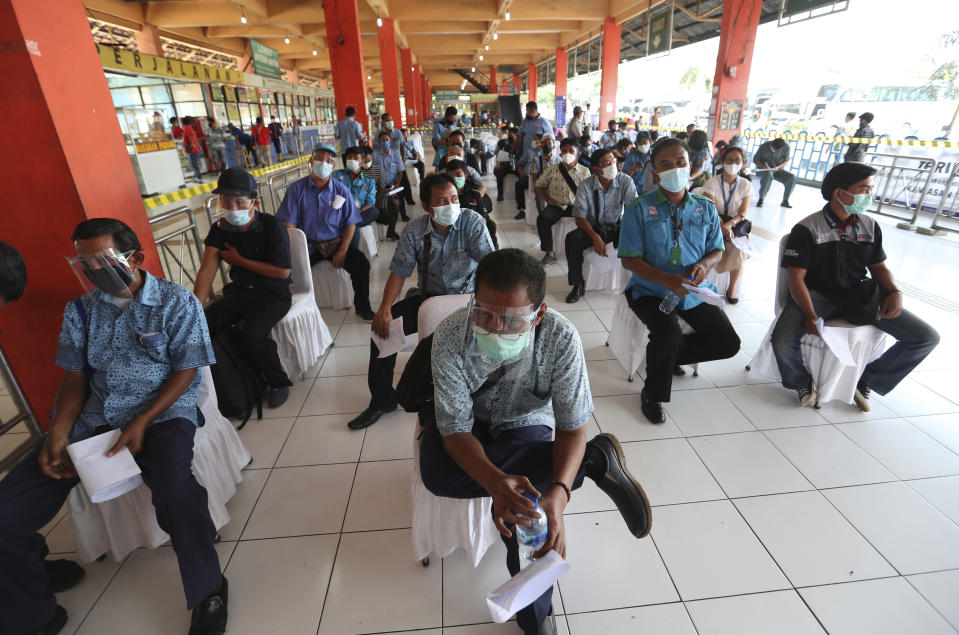 Transportation workers wear face masks and shields to help curb the spread of the coronavirus while waiting for the AstraZeneca vaccine during a mass vaccination campaign for public transport workers at the Kampung Rambutan Bus Terminal in Jakarta, Indonesia, Thursday, June 10, 2021. (AP Photo/Achmad Ibrahim)