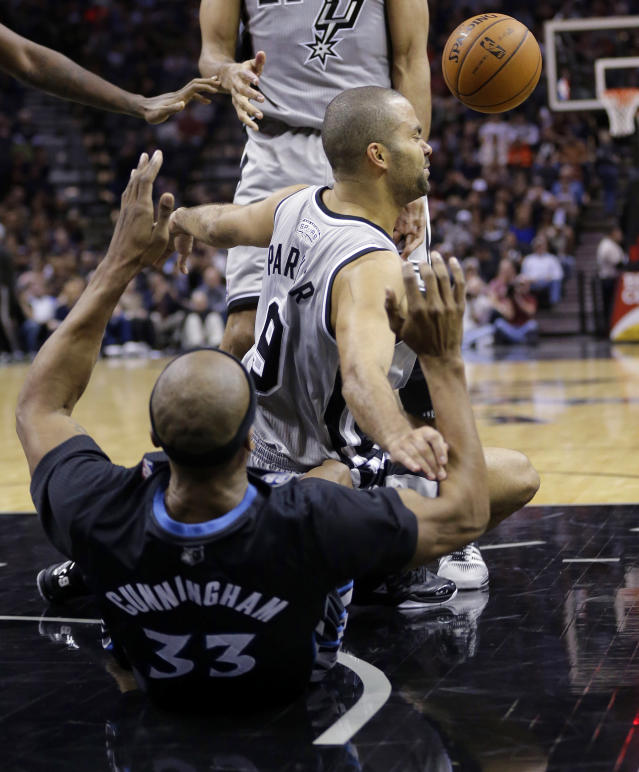 San Antonio Spurs' Tony Parker (9), of France, crashes into Minnesota Timberwolves' Dante Cunningham (33) while trying to score during the first half of an NBA basketball game on Sunday, Jan. 12, 2014, in San Antonio. Parker was called for charging. (AP Photo/Eric Gay)