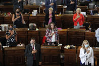 FILE - In this June 3, 2020, file photo, State Representatives stand at their desks during the Pledge of Allegiance in the Iowa House chambers, at the Statehouse in Des Moines, Iowa. As states brace for a coronavirus surge following holiday gatherings, one place stands out as a potential super-spreader site, the statehouses where lawmakers will help shape the response to the pandemic. (AP Photo/Charlie Neibergall, File)