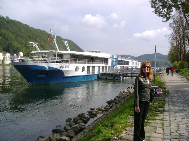 This 2012 photo shows Betty Adams in Passau, Germany, with the MS Bolero, a Viking River Cruises ship. Adams took a cruise on the Danube River with her husband Glenn Adams but the couple missed a connection with a flight en route to the first departure port. They took a next-day flight and managed to get to the ship in time, but they were glad to have travel insurance to cover costs associated with the scrambled plans. Many travel experts recommend insurance for complicated itineraries, including cruises.  (AP Photo/Glenn Adams)