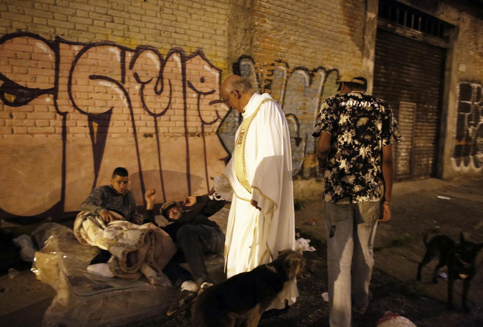 Priest Julio Lancellotti talks with homeless people on the street as he invites them to a free Christmas dinner at Sao Miguel Arcanjo church in Sao Paulo December 24, 2014. Picture taken December 24, 2014. REUTERS/Nacho Doce (BRAZIL - Tags: SOCIETY POVERTY RELIGION)