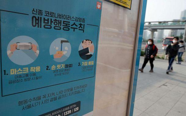 PHOTO: People wearing face masks walk near a banner showing precautions against the novel coronavirus at a bus stop in Seoul, South Korea, on May 25, 2020. (Lee Jin-man/AP)