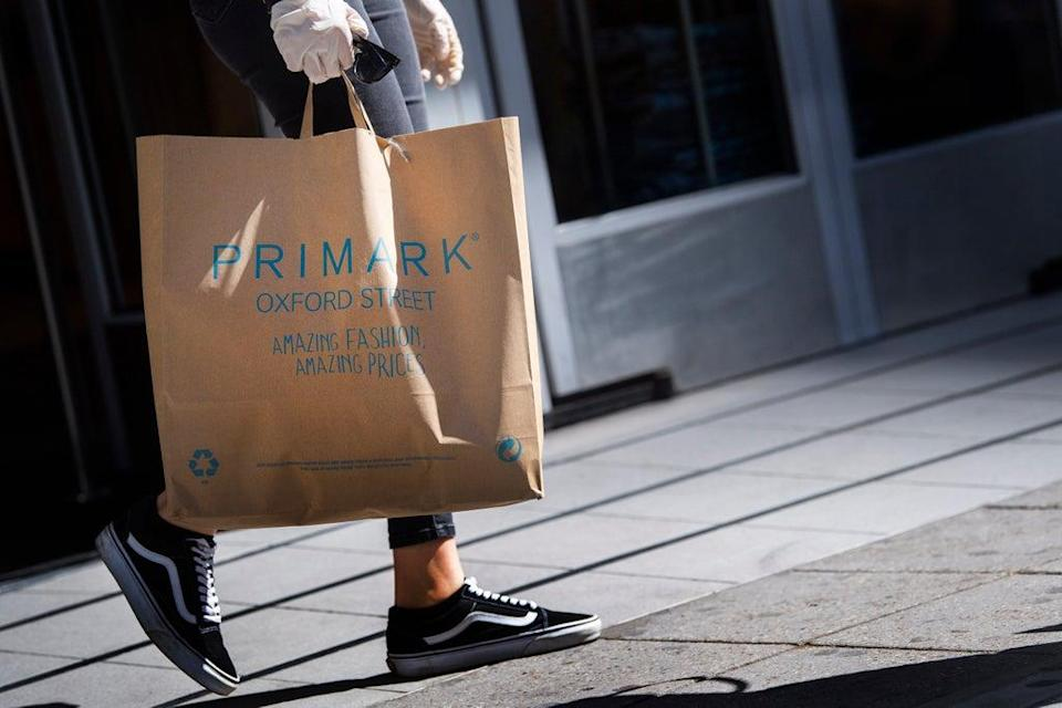 A customer carries bags of shopping as they leave Primark in Oxford Street (Victoria Jones/PA) (PA Archive)