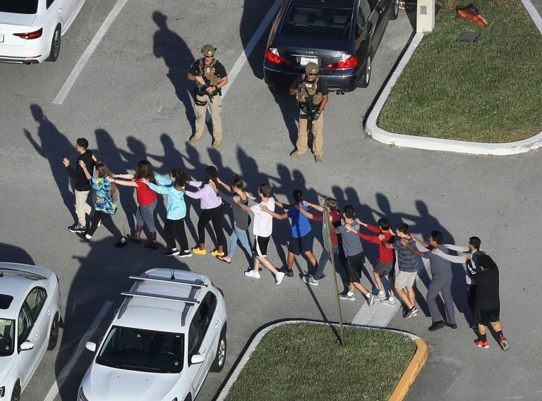 Students and staff are brought out of the Marjory Stoneman Douglas High School in Florida after the February 14, 2018 deadly shooting