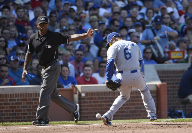 Los Angeles Dodgers third baseman Jerry Hairston Jr. makes a fielding error on a ground ball hit by Chicago Cubs Cody Ransom as third base umpire Alan Porter signals a fair ball during the second inning of a baseball game, Saturday, Aug. 3, 2013 in Chicago. (AP Photo/Brian Kersey)