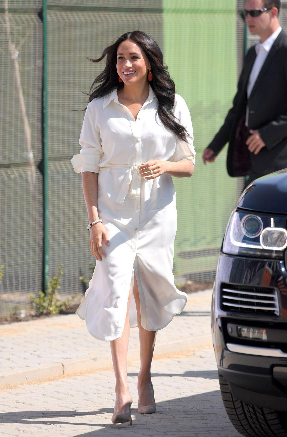 """<p>Perhaps a white shirt dress is more your speed. The Duchess wore this take on the button down while visiting Johannesberg, South Africa. The garment is by local brand Hannah Lavery, whose site now calls it the """"Meghan dress."""" Here, find the original dress (which has been known to sell out), plus a few similar options. </p><p><a class=""""link rapid-noclick-resp"""" href=""""https://www.hannahlavery.co.za/collections/dresses/products/tencilshirtdress"""" rel=""""nofollow noopener"""" target=""""_blank"""" data-ylk=""""slk:Shop Now"""">Shop Now</a></p><p><a class=""""link rapid-noclick-resp"""" href=""""https://go.redirectingat.com?id=74968X1596630&url=https%3A%2F%2Fwww.jcrew.com%2Fus%2Fp%2Fwomens_category%2Fdressesandjumpsuits%2Frelaxedfit-crisp-cotton-poplin-shirtdress%2FAY158&sref=https%3A%2F%2Fwww.townandcountrymag.com%2Fsociety%2Ftradition%2Fg36386449%2Fmeghan-markle-white-button-down-shirts%2F"""" rel=""""nofollow noopener"""" target=""""_blank"""" data-ylk=""""slk:Shop a Similar Style"""">Shop a Similar Style</a></p><p><a class=""""link rapid-noclick-resp"""" href=""""https://go.redirectingat.com?id=74968X1596630&url=https%3A%2F%2Fwww.bergdorfgoodman.com%2Fp%2Flagence-cameron-linen-long-shirtdress-prod165150084&sref=https%3A%2F%2Fwww.townandcountrymag.com%2Fsociety%2Ftradition%2Fg36386449%2Fmeghan-markle-white-button-down-shirts%2F"""" rel=""""nofollow noopener"""" target=""""_blank"""" data-ylk=""""slk:Shop a Similar Style"""">Shop a Similar Style</a></p><p><a class=""""link rapid-noclick-resp"""" href=""""https://go.redirectingat.com?id=74968X1596630&url=https%3A%2F%2Fveronicabeard.com%2Fproducts%2Fcita-dress&sref=https%3A%2F%2Fwww.townandcountrymag.com%2Fsociety%2Ftradition%2Fg36386449%2Fmeghan-markle-white-button-down-shirts%2F"""" rel=""""nofollow noopener"""" target=""""_blank"""" data-ylk=""""slk:Shop a Similar Style"""">Shop a Similar Style</a></p>"""