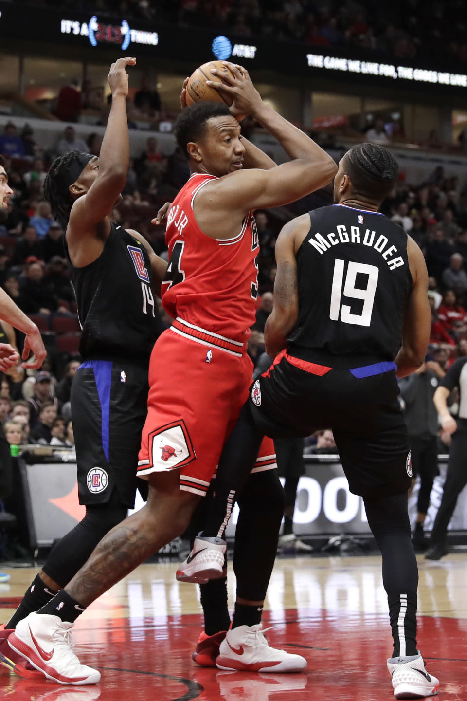 Chicago Bulls center Wendell Carter Jr., center, looks to pass against Los Angeles Clippers guard Terance Mann, left, and guard Rodney McGruder during the first half of an NBA basketball game Saturday, Dec. 14, 2019, in Chicago. (AP Photo/Nam Y. Huh)