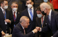 U.S. President Joe Biden, right, is greeted by Turkey's President Recep Tayyip Erdogan, center, during a plenary session at a NATO summit in Brussels, Monday, June 14, 2021. (AP Photo/Olivier Matthys, Pool)
